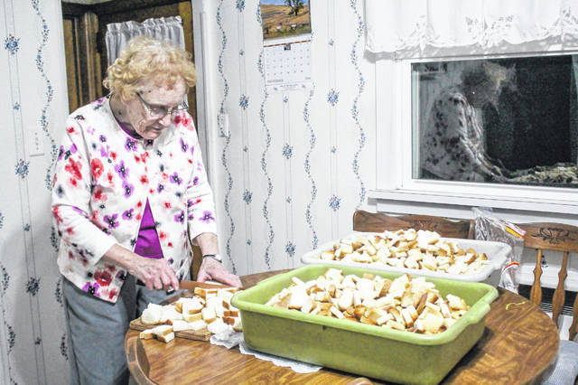 The window of her rural Maria Stein home reflects Mary Dahlinghaus as she cuts up bread for Thanksgiving dressing. The pans hold half the 24 pounds of bread she uses to prepare the holiday meal for the 500 guests expected at this year's Thanksgiving Fellowship in Minster.