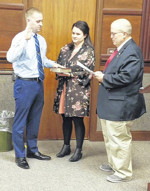 Sidney's newest police officer, Nathan Wisniewski, left, was sworn-in by City Manager Mark Cundiff Monday night. Wisniewski's his wife, Megan, held the bible during the ceremony at the Sidney City Council meeting.