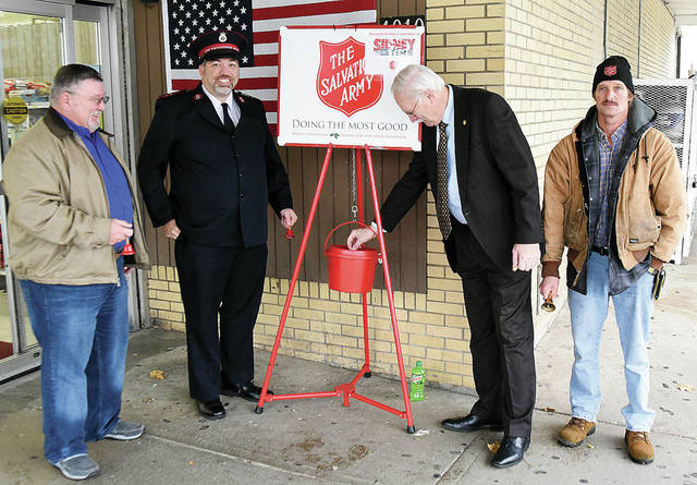 Sidney Mayor Mike Barhorst, second from right, makes a contribution to open this year's Salvation Army red kettle campaign in front of Sidney Foodtowne. Watching, left to right, are Shelby County Commissioner Bob Guillozet, Salvation Army Capt. Joseph Hansen and bell-ringer Michael Hines.
