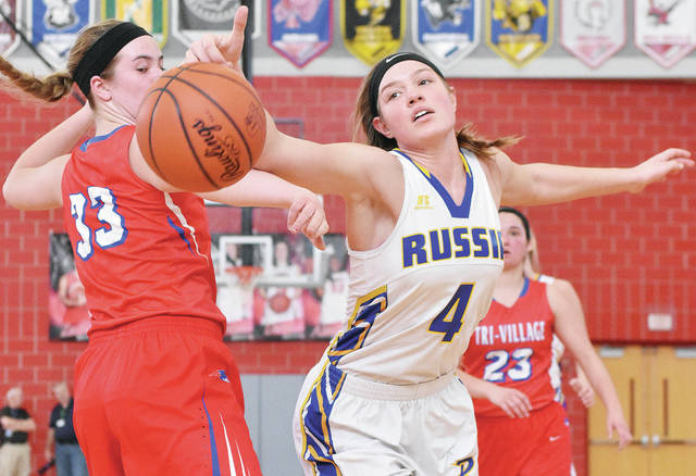 Russia's Laurissa Poling, right, and Tri-Village's Maddie Downing reach for a loose ball during a Division IV district final at Troy's Trojan Activities Center on March 3. Poling is one of several returning all-district players.