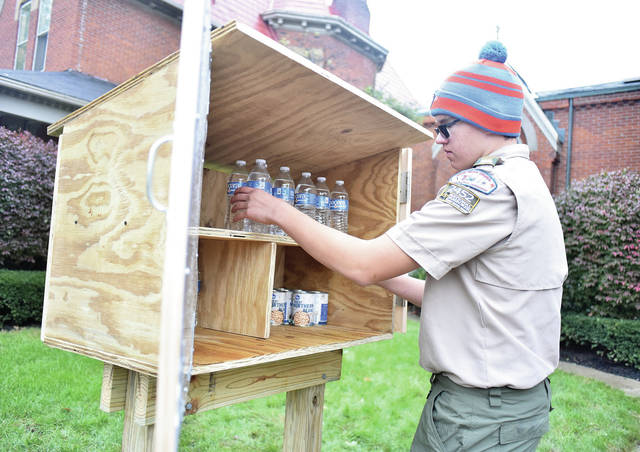 "Mason Hughes, 14, of Piqua, son of Bridget and Jeff Hughes, stocks his ""Community Blessing Box"" which he built as an Eagle Scout project in front of the First Presbyterian Church, Saturday, Oct. 27."