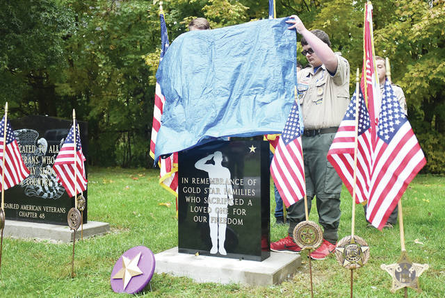 Sidney Boy Scout Troop 97 members Thomas Sibert, left, 14, son of Tara and Rob Sibert, and Mason Rose, 14, both of Sidney, son of Dianne and Jeff Rose, unveil the Gold Star memorial during a dedication ceremony at Graceland Cemetery Saturday, Oct. 27.