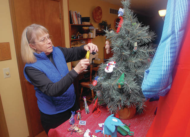 Janet Aselage, of Sidney, trims a tree with ornaments made by a women's group in Guatemala. They will be for sale at the Fair Trade and More Christmas Boutique, Nov. 17-18.
