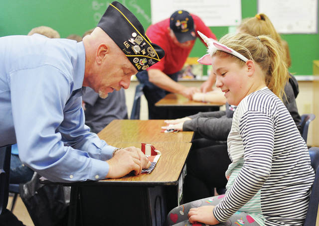 Desert Storm veteran Jon Egbert, left, helps Kyla Egbert, 10, both of Anna, daughter of Shawn and Rachelle Egbert, fold a U.S. flag during a flag folding presentation at Anna Elementary by U.S. veterans Wednesday, Nov. 7. Each 5th grade student was given a small flag to fold. The flags were taken from the graves of veterans. Kids learned that the flag is folded 13 times and that each fold has been given meaning.