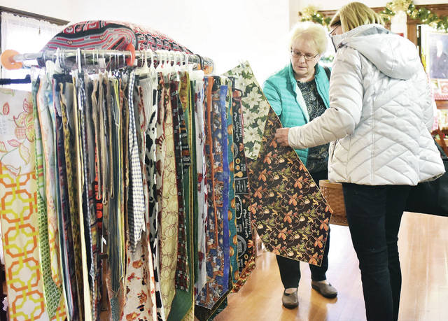 Jane Perryman, left, of Minster, and Linda Keller, of Sidney, look at reversible table runners for sale during the Angels in the Attic Craft Show held at the Ross Historical Center Thursday, Nov. 8.