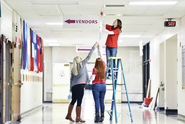 Putting up signs for the Charity League Annual Craft Festival at Lehaman Catholic High School are, left to right, festival chair Ali Rittenhouse, of Sidney, festival co-chair Kristi Berning, of Anna, and Jenni Koltak, of Sidney. The festival is Saturday, Nov. 10 from 9 a.m. to 3 p.m.. Vendors will fill the gym and hallways selling their wares.