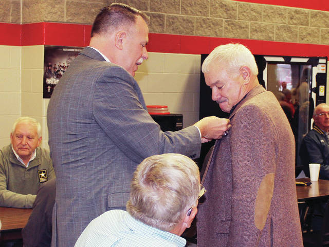 Director of the Ohio Department of Veterans Services Chip Tansill, left, pins U.S. veteran Crag Fogt during an annual veterans program put on by the Fort Loramie Old School History Club. Tansill also spoke during the event at Fort Loramie High School, Friday, Nov. 9. Vietnam Era veterans were pinned in recognition of the 50th anniversary of the Vietnam War.