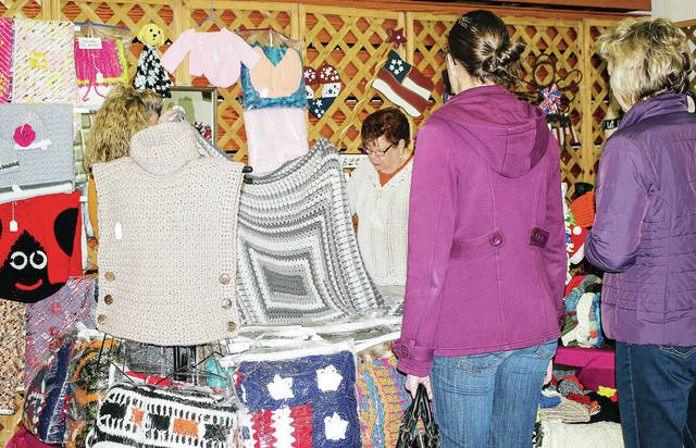 Brenda Luthman, left to right, and Sally Behr, both of Fort Loramie, display one of their afghans for Amy Cain, of Anna, and Jane Pleiman, of Fort Loramie, at the Charity League Annual Craft Festival at Lehman Catholic High School Saturday, Nov. 10.