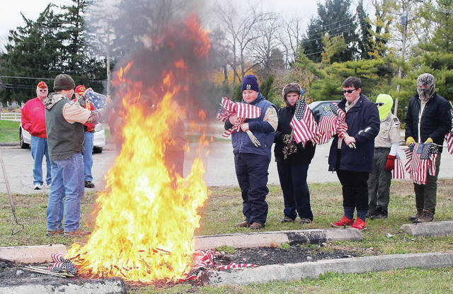 Boy Scouts ceremoniously burn U.S. flags that had been placed on the graves of war veterans Saturday, Nov. 10 behind the IUE Hall.