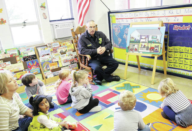 Lieutenant A. McLain teaches Mrs. Jane Ulrich's 3-4 year old ( nursery K - prep ) class at sidney Cooperative nursery school about fire safety recently.