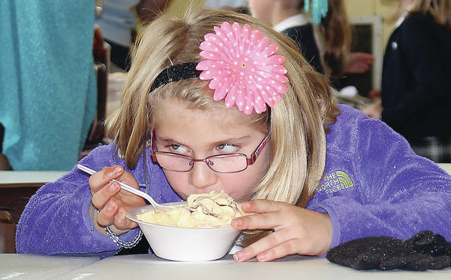 Second grade student Mena Neu, 8, of Sidney, daughter of Emily and Justin Neu, eats ice cream during an ice cream fundraiser at Holy Angels for veterans Thursday, Nov. 8.