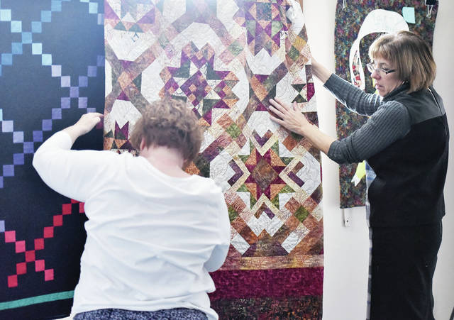Gateway Arts Council (GAC) assistant Susan Clark, left, of Sidney, and GAC Executive Director Ellen Keyes hang one of the quilts that will be on display in the Loose Threads and Sanded Edges art show opening Friday, Nov. 16. The opening will be from 6 to 8 p.m.. The quilts have been made by the Loose Threads Quilt Club. Handmade wood furniture will also be on display created by Gene Hoellrich, of Sidney. Admission to the show is free.