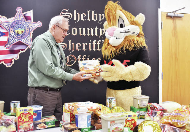 Shelby County Sheriff John Lenhart, left, and Daren the D.A.R.E Lion sort through food items while preparing food baskets for the approaching Thanksgiving holiday. Fifth grade students from the Botkins, Fort Loramie, Hardin-Houston and Jackson Center School districts recently completed a good citizenship assignment while participating in the (Drug Abuse Resistance Education) D.A.R.E. program. The good citizenship assignment required each student to earn one dollar by completing an extra chore at home. Each student then donated their earnings to pay for the food used for the food baskets. The Sidney-Shelby County Salvation Army provided the names of four families requesting assistance, to receive the holiday food baskets. This will be the sixth consecutive year for the good citizenship project and continues to be very successful.
