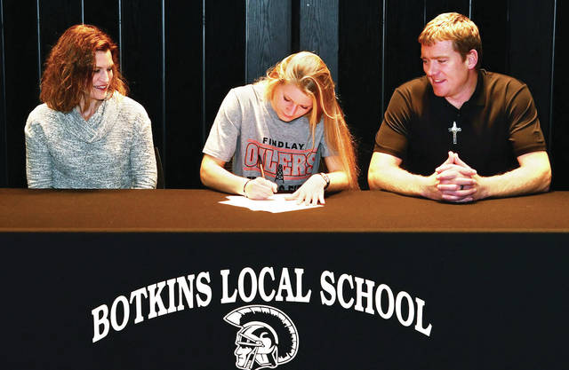 Adriana Jutte, center, signs a national letter of intent to participate in track Findlay University as her mother Stacey Jutte, left, and father Rick Jutte watch at Botkins' cafetorium on Monday.