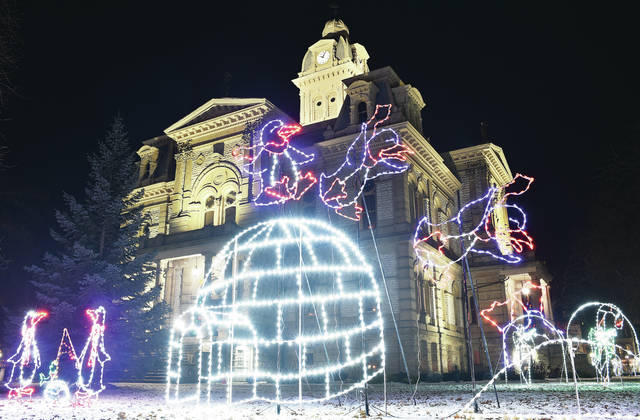 Christmas lights depict a penguin falling off its igloo and headfirst into a snow bank on the courtsquare Wednesday, Nov. 28.