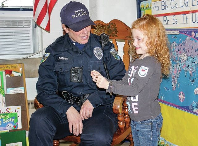 Sidney Police Officer Valerie Leigeber, left, uses Averie Varno, 4, of Sidney, daughter of Ray and Ann Wise to demonstrate the use of handcuffs at the Sidney Cooperative Nursery School Friday, Nov. 30. Leigeber gave a talk to kids at the nursery about what it is like being a police officer.