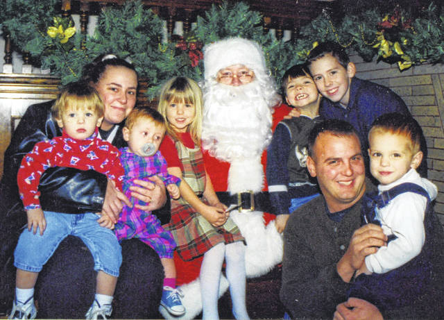 The first year: In 2000, Candy Huber's grandchildren — and two of her children — pose with Santa for a Christmas card shot during the Shelby County Historical Society's inaugural Christmas of Yesteryear program, in the Ross Historical Center in Sidney. Pictured from left are Tanner Smedley, Tracy Littleton, Chloe Littleton, Victoria Smedley, Santa, Hunter Smedley, Marc Burdiss, Robert Smedley and Alex Burdiss.