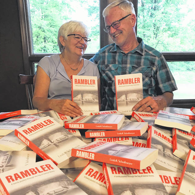"""Linda and Steve Schmitmeyer smile at one another as they each hold a copy of Linda's book, """"Rambler: A Family Pushes Through the Fog of Mental Illness."""" She and Steve will be discussing their experience with Steve's illness on Saturday, Nov. 24, from 1 to 2:30 p.m. at Amos Memorial Public Library."""