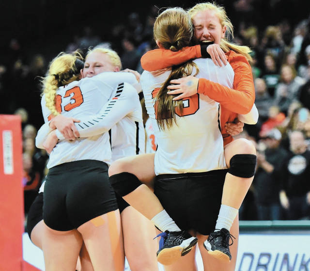 Versailles' Lindsey Winner, in white, holds Caitlin McEldowney, in orange, after McEldowney jumped into her arms while they celebrated after winning the Division III state championship on Saturday at Wright State's Nutter Center in Fairborn.