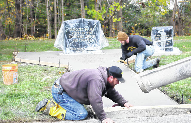 Alan Saintignon, left, of New Breman, and Dave Nagel Jr., of Sidney, both of Dave Nagel Excavating, install a cement walkway in Graceland Cemetery in Sidney, recently. The firm donated labor and equipment and Spring Creek Corp. donated the cement. The walkway will allow handicap access to the new veterans memorial in the cemetery.