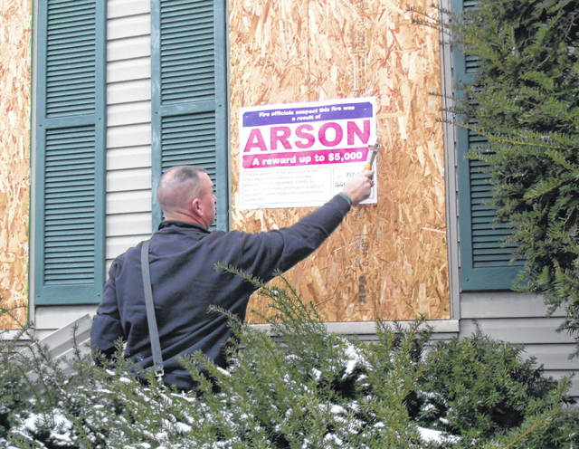 Sidney Fire Lt. Jason Truesdale posts the Ohio Blue Ribbon Arson Committee reward sign on a boarded up window in the front a house consumed by an arson fire at 311 S. Miami Ave. on Oct. 8.