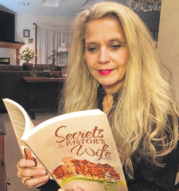 "Christina Ryan Claypool reads a copy of her book, ""Secrets of the Pastor's Wife: A Novel."""