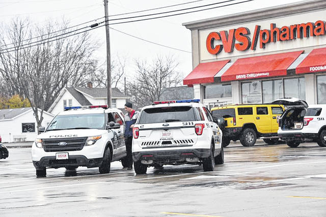 Sidney Police convene in the parking lot of the CVS Pharmacy in Sidney, Monday, Nov. 26, to apprehend a robber who stole $1,000 worth of drugs.