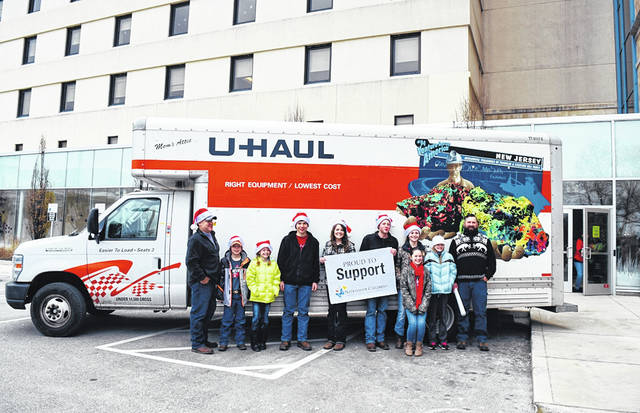 Organizers Tyler and Monica Slaven, of DeGraff, along with fellow volunteers are ready to unload the 3,000 toys they collected for last year's toy drive.