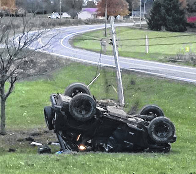 A Jeep Wrangler sits on its top after Bryce Alan Mills, 19, of Fletcher, hit a utility pole causing the vehicle to flip.