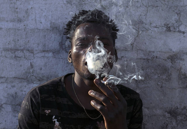 "FILE - In this Tuesday, Sept. 18, 2018, file photo, a Malawian migrant Jonas smokes marijuana on the rooftop of an abandoned building in downtown Johannesburg. 2018 has been called the ""year for cannabis"" in South Africa. But there are still hurdles before a legal marijuana industry can flourish in an African economic power deemed ideal for large-scale cultivation. (AP Photo/Bram Janssen, File)"