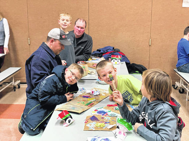 Cub Scout Pack 301, of Anna, completes a craft during a recent meeting. Pictured are, left of table, front to back, Trent Leugers, Eric Leugers, Gavin Albers, Kevin Albers; right of table, back to front, Connor Bertke, Eli Pence.