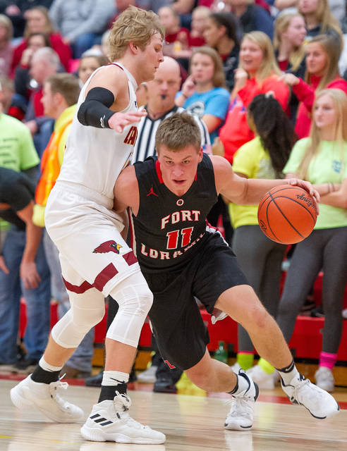 Fort Loramie junior guard Nick Brandewie dribbles with pressure from New Bremen's Brandon Heitkamp during a nonconference game on Saturday in New Bremen.