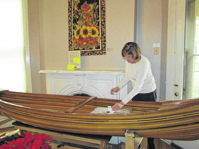 Ellen Keyes, executive director of Gateway Arts Council, adds raffle ticket stubs to the box from which a winner's name will be drawn, April 13. The box is in a handcrafted, wooden canoe, which is the raffle prize. It's on display in the council gallery, 216 N. Miami Ave.