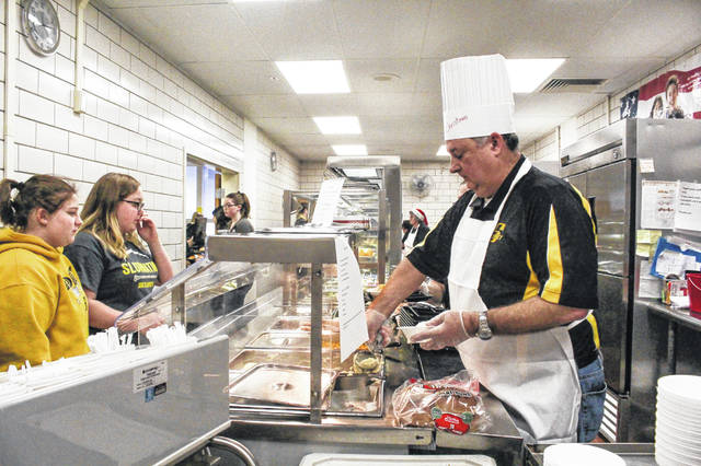 Sidney City Schools Superintendent Bob Humble serves up lunch to Sidney High School students in the school cafeteria, Tuesday, Dec. 18.