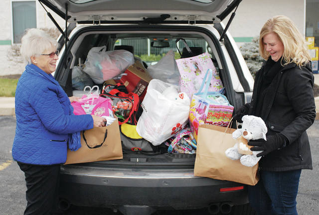 Barri Grandey, left, president of Delta Kappa Gamma, and Cindy Trent, women's health nurse practioner at Wilson Health OB-GYN, look through items donated to Shelby County Job and Family Services for use by foster children, Thursday, Dec. 14, in Sidney.