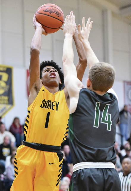 Sidney junior guard Dominick Durr shoots with pressure from Greenville's Jordan Dill during a Greater Western Ohio Conference American North Division game on Friday in Sidney.
