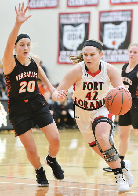 Fort Loramie junior forward Marissa Meiring dribbles with perssure from Versailles' Danielle Kunk during a nonconference game on Saturday in Fort Loramie. Meiring led Fort Loramie with 15 points and four steals.