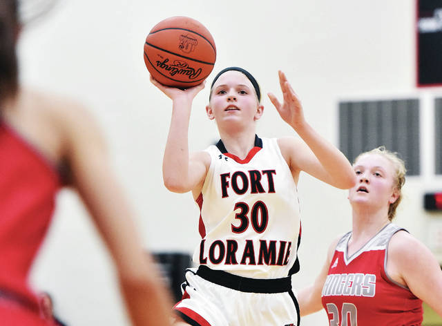 Fort Loramie's Dana Rose takes a jump shot followed by New Knoxville's Megan Jurosic at Fort Loramie Thursday.