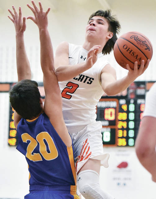 Minster's Jack Heitbrink shoots over Russia's Will Sherman during a nonconference game on Friday in Minster.