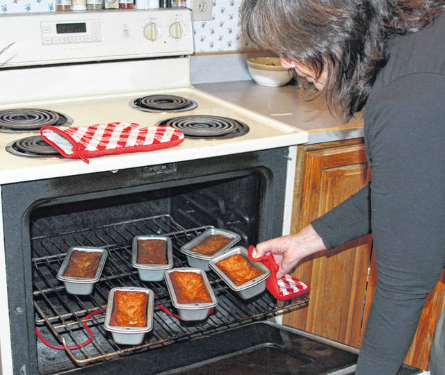 Darlene Clayton, of Sidney, removes a batch of freshly-baked fruitcakes from the oven.