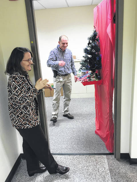 Finance Officer Ginger Adams and Information Technology Manager Joel Glass find humor in the photos on the electronic tablet as they scroll across the screen on the door that tied for first place in the city of Sidney's annual Christmas Door Decorating Contest.