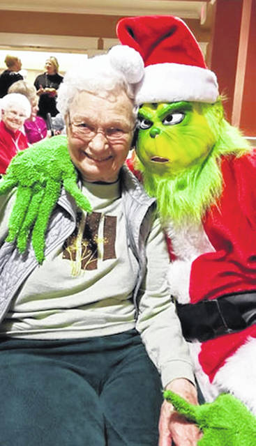Rita Harting, of New Bremen, gets a hug from the Grinch during a resident family Christmas celebration at Elmwood of New Bremen, recently.