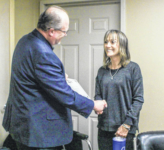 Joe Braden, right, of the Auditor of State's office greets Nancy Spence, financial director of Shelby Metropolitan Housing Authority, Monday, Dec. 17, in Sidney, before presenting her with an Auditor of State Award.
