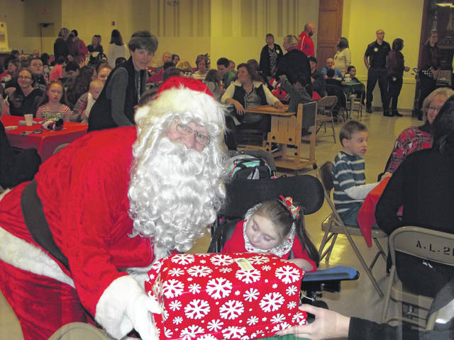 Jaycie Butts, 5, daughter of Kristen and Dave Butts, of Jackson Center, receives her present from Santa Claus during the 79th annual Sidney Rotary Christmas party. More than 250 children, parents, guardians, teachers, aides and Rotary members attended the party Monday at the Sidney American Legion.