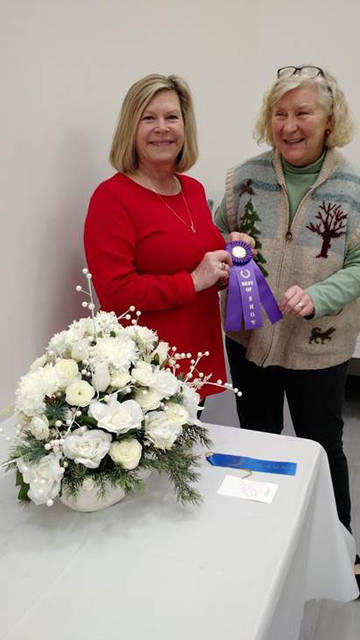 Julie Gilardi, left, of Sidney, accepts the Best of Show ribbon from judge Marian Moeckel at a Christmas Flower Show hosted by the Rainbow Gardeners of Shelby County. The Dec. 11 show at the Amos Memorial Public Library featured nearly 50 Christmas-themed floral arrangements. Gilardi's all-white arrangement also won the People's Choice award based on votes by attendees. Jenny Jones, of Sidney, won the drawing for a holiday gift basket.