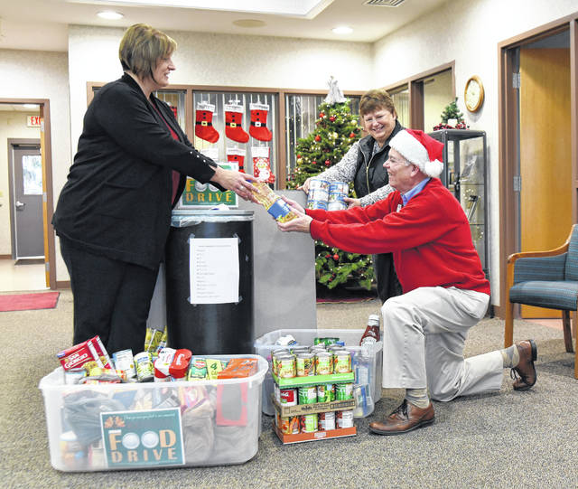 Mike Monnier, right, president/CEO of OSB Bancorp Inc., takes a bottle from Osgood State Bank Fort Loramie Branch Manager Angela Skirvin, left, as they and bank teller Michelle Gayer, of Minster, pack up food at the branch, Monday, Dec. 10. The food was donated by customers during the bank's recent food drive for charity. The branch will celebrate Monnier's retirement, Dec. 19.
