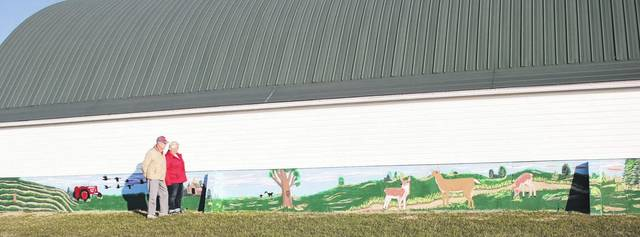 Bud and Pauline Meyer, 2400 Stillwater Road, Houston, look at the scene on the barn their daughter, Shirley Arnett, painted for them. The scene includes a tractor in the field with geese flying overhead, a barn and tree with animals in the background, deer and a pond. Pauline said her daughter likes to paint in the style of artist Bob Ross.