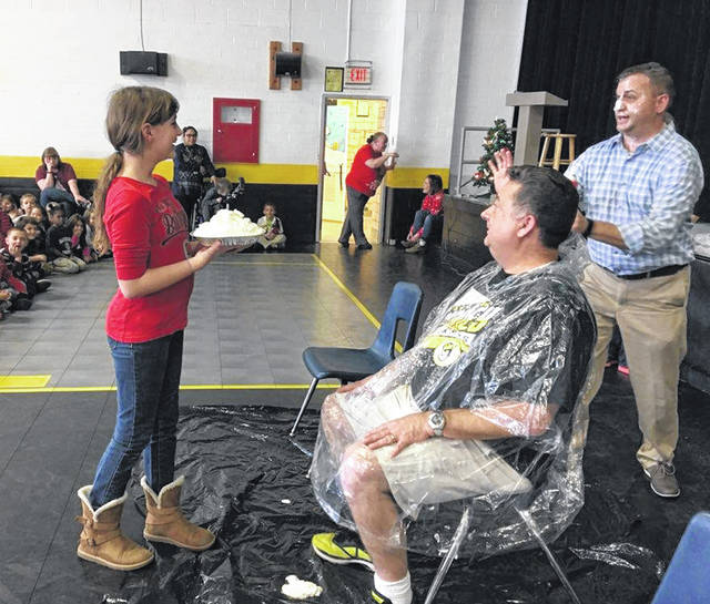 Sidney City Schools Superintendent Bob Humble was a good sport Tuesday when Northwood students Northwood Elementary School fifth-graders Lauren Westgerdes, Kylie Harrod and Makayla Perkins got to throw pies in his face. In the photos, left to right, Northwood Principal Eric Barr, who also received a pie in the face, gives directions to Lauren before putting the pie in Humble's face; then Lauren successfully place the pie in Humble's face. Finally Barr checks out the students' work as Humble attempts to remove some of the pie.