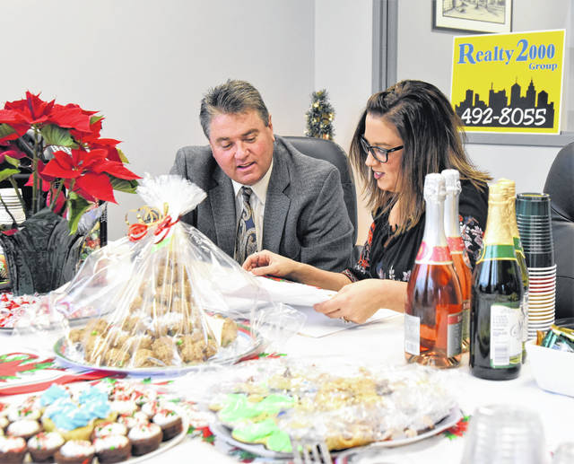Tim Gleason, left, broker and owner of Reality 2000, celebrates the grand opening of his new location at 100 S. Main Ave., Sidney, with office administrator Nikki Loudenback, Friday, Dec. 21. Gleason has 30 years' experience in the real estate business, while Loudenback has 12 years.