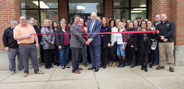 Tim Gleason, center left, owner of Realty 2000, and Sidney Mayor Mike Barhorst cut the ribbon on new offices for the real estate firm, Friday, Dec. 21, in downtown Sidney.